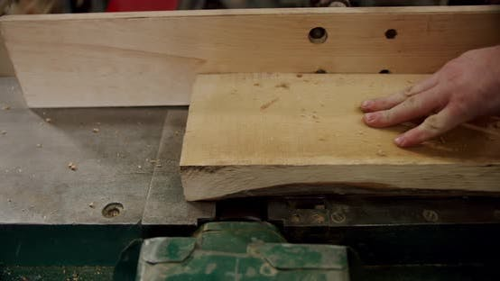 Worker in a Woodworking Workshop Takes a Board and Puts It on a Machine in Woodworking Workshop of a