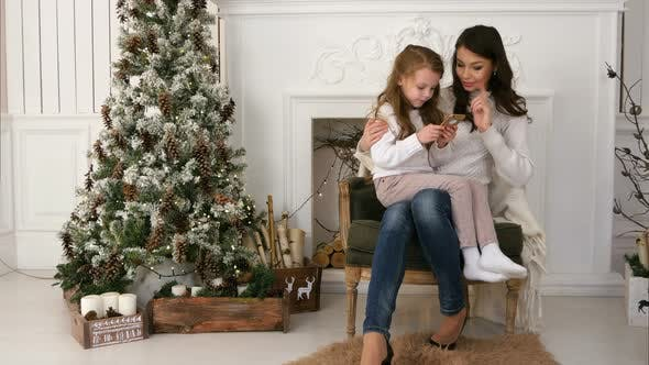 Thumbnail for Mother Showing Her Little Daughter How To Type a Message To Santa on the Phone