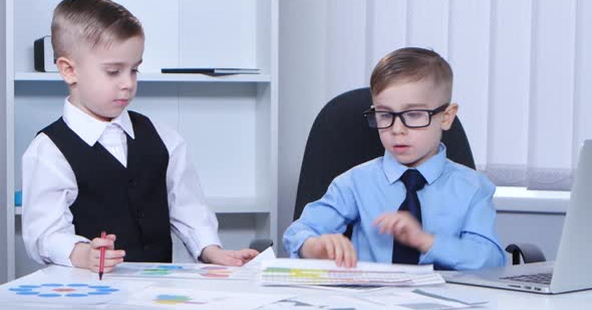Two Little Boys Businessman in the Office Consider Graphs and Charts