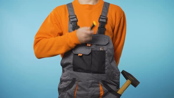Body Shot of Man in Workwear with Screwdriver in His Hands