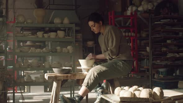 Craftswoman Is Sitting On Potter's Wheel and Making Bowl