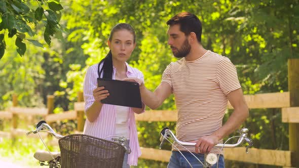 Thumbnail for Couple with Tablet Pc and Bicycles at Summer Park