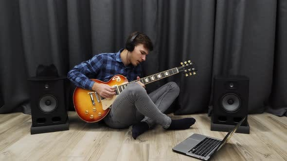 Thumbnail for Man playing on electric guitar wearing headphones practicing song in home music recording studio