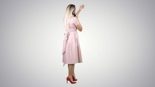 Cover Image for Standing young beautiful girl making a call on gradient background.