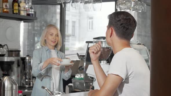 Thumbnail for Schöner junger Mann lächelnd auf die Kamera beim Genießen seines Kaffees im Café