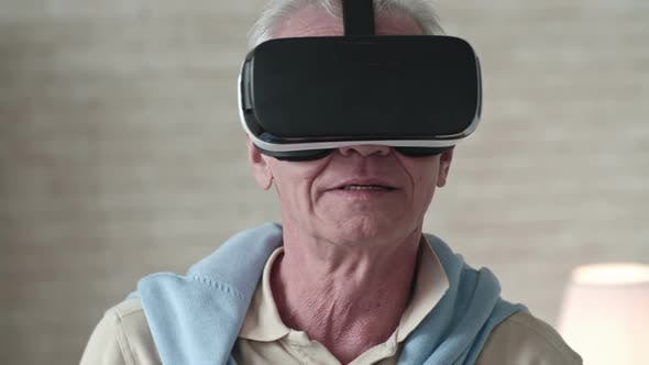 Thumbnail for Curious Elderly Man Looking Around in VR Headset