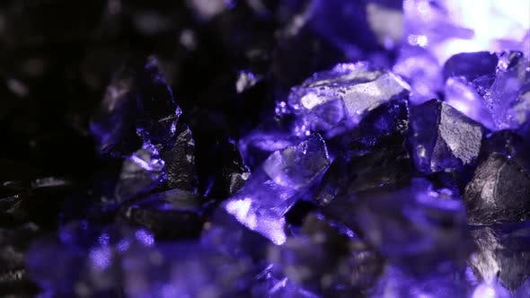 Thumbnail for Purple glow shining off small rocks spinning