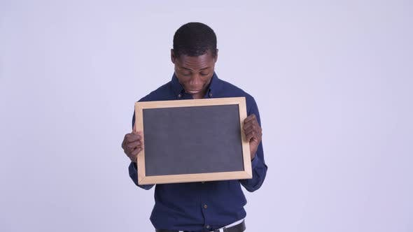 Young Happy African Businessman Holding Blackboard and Looking Surprised