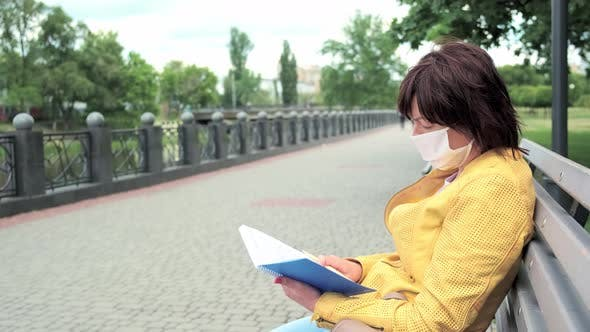 Thumbnail for Woman in a Protective Mask Sits on a Park Bench and Takes Notes in Her Notebook.