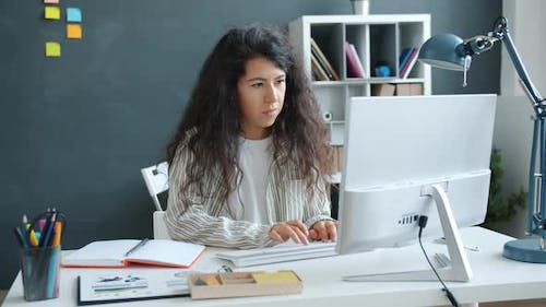Serious Businesswoman Working in Creative Office Using Computer Writing in Notebook