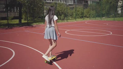 Young Girl in Sneakers, Skirt and T-shirt Riding Yellow Skateboard on an Outdoor Basketball Court