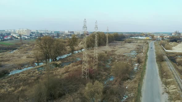 High-voltage electric power poles in field. Drone shot of transmission towers