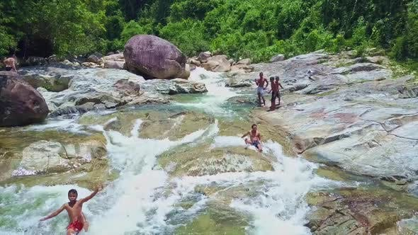 Thumbnail for Flycam Shows Happy Asian Boys Playing in Mountain River