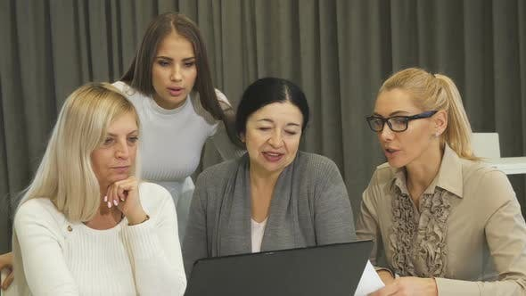 Cover Image for Beautiful Young Businesswoman Using Laptop During Business Meeting with Colleagues
