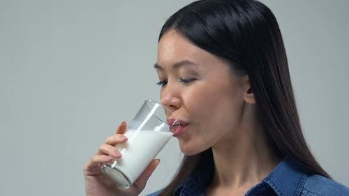 Beautiful Asian Woman Drinking Glass of Milk, Healthy Diet, Essential Nutrients