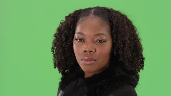 Thumbnail for Close up of pretty black female with curly hair looking at camera on greenscreen