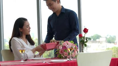 Romantic Couple Giving Gift to Lover at Restaurant