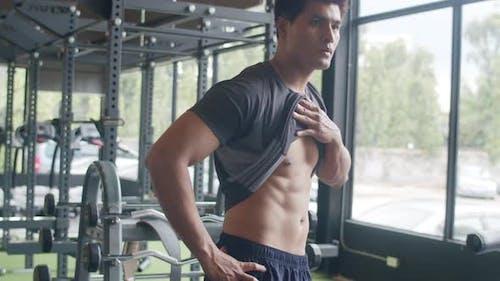 Hübscher asiatischer Kerl nimmt Hemd nackten Torso Körper Blick auf seine Muskeln und trainierten Körper.