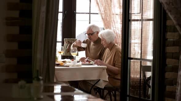 60-Something Caucasian Couple Having Emotional Talk at Breakfast