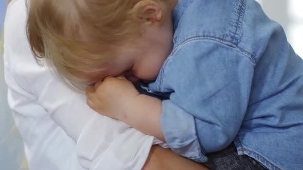 Thumbnail for Young Mother Holding Sleepy Blond Baby