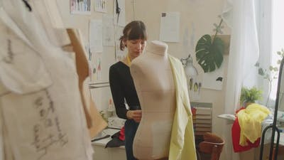 Female Dressmaker Attaching Fabric to Dress Form