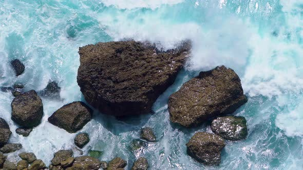 Top View of the Ocean Shore with Waves Crashing on Rocks
