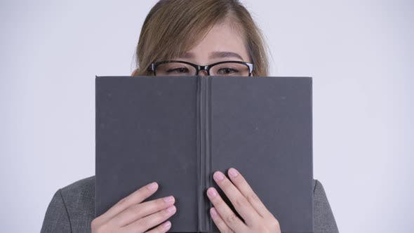 Cover Image for Young Shy Asian Businesswoman Thinking While Covering Face with Book