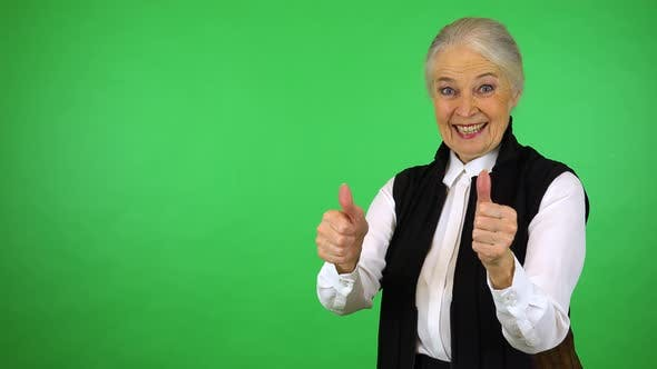 Thumbnail for An elderly woman smiles and shows a double thumb up to the camera - green screen studio