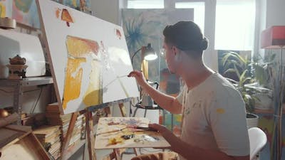 Portrait of Cheerful Male Artist Paining in Studio