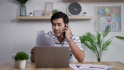 Asian businessman talking on smartphone in home office