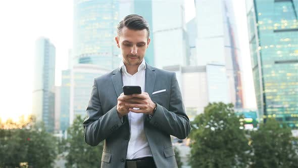 Thumbnail for Young Caucasian Man Holding Smartphone for Business Work.
