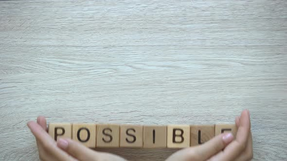 Thumbnail for Possible, Hands Pushing Word on Wooden Cubes, Possibilities Motivation and Goals
