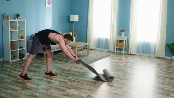 Young Man Is Spreading Fitness Mat in Living Room