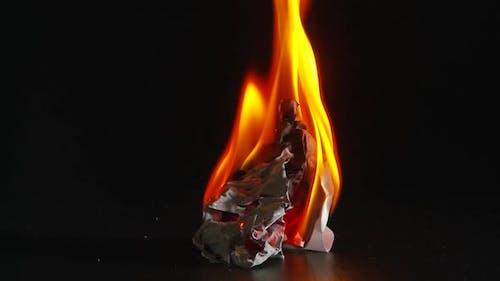 ball of white paper burning then smoldering