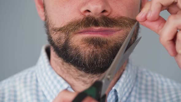 Bearded Man Twists His Mustache and Cuts It Off with Scissors