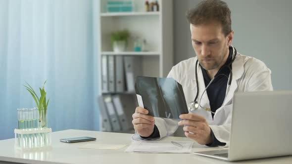 Thumbnail for Aufmerksamer Chirurg mit Blick auf Knochenröntgen und E-Mail an Patienten auf dem Laptop senden