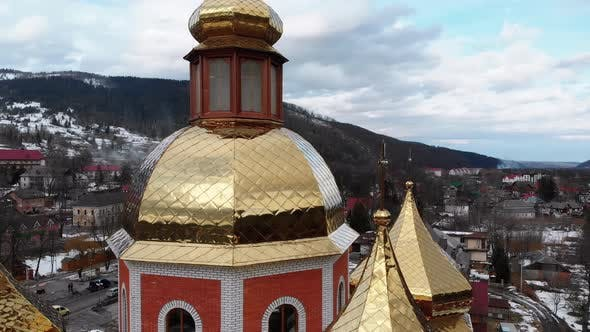 Aerial Drone View of Ukrainian Church with Golden Domes in Carpathian Village in Winter