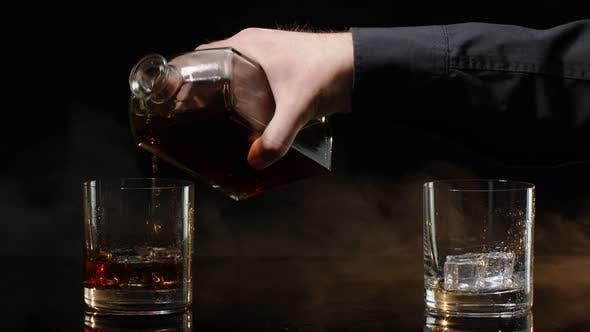 Barman Pour Golden Whiskey Cognac Brandy From Bottle Into Glasses with Ice Cubes on Dark Background