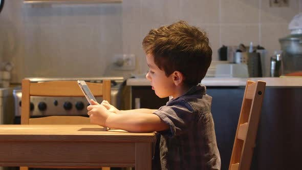 Thumbnail for Cute Little Child Uses A Tablet Pc At A Table At Home. Casual Clothes