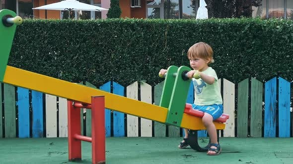 Thumbnail for Kid Boy having Fun to Play on Children Playground