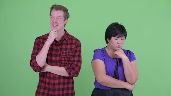 Thumbnail for Stressed Overweight Asian Woman with Happy Scandinavian Hipster Man Thinking Together