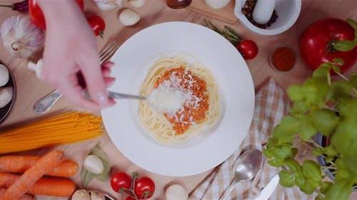 Person Garnishing Spaghetti With Cheese