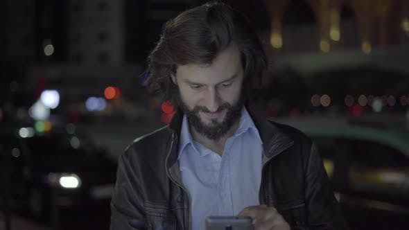 Thumbnail for Happy Caucasian Man Using Smartphone in Night City