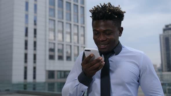 Thumbnail for Dark-skinned Businessman Chatting Online on Phone