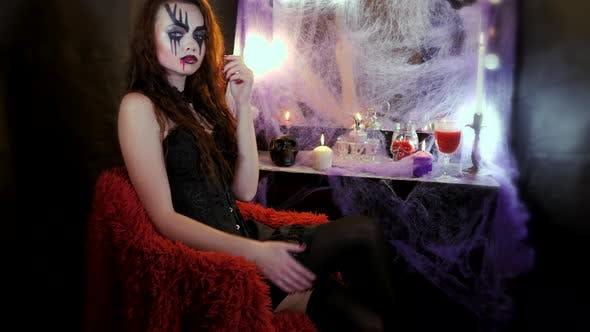 Cover Image for Girl with Makeup for Halloween Is Sitting in Front of a Mirror. Girl Throws Her Leg Over Her Leg and