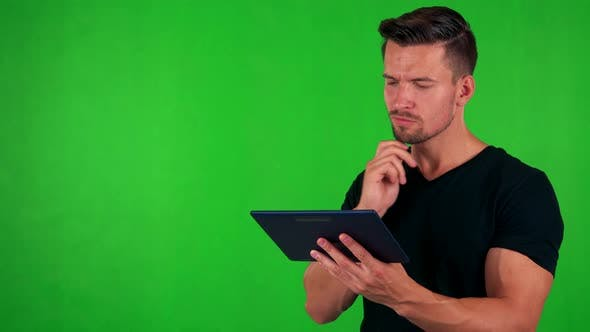 Thumbnail for Young Handsome Caucasian Man Works on Tablet - Green Screen - Studio