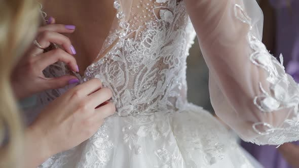 Thumbnail for Bridesmaid Ties and Helps Put on Wedding Dress. Morning Preparation of the Bride with White Gown