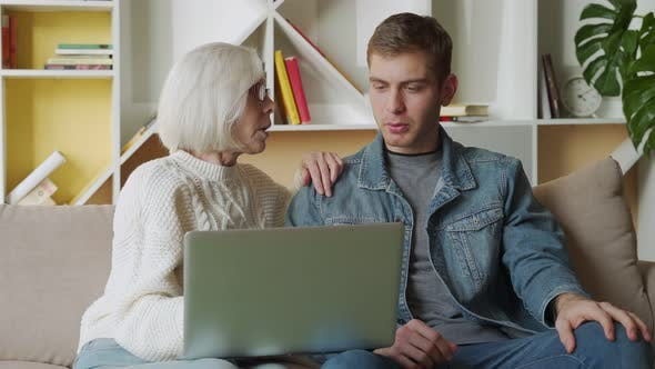 Thumbnail for Middle Aged Man Helping His Mother Use a Laptop Computer at Home