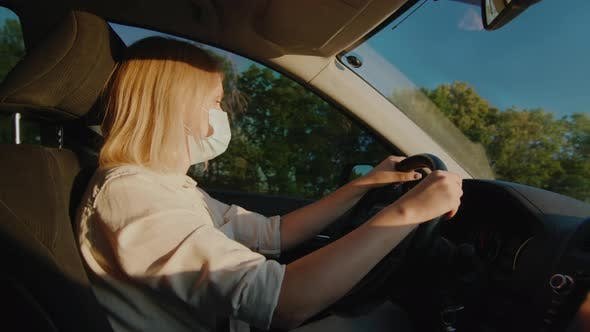 Thumbnail for Driver in Protective Mask Drives Behind the Wheel of a Car