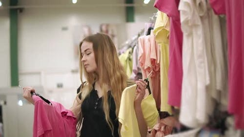Teenage Girl is Holding Two Hunger with Tshirts in a Hall of Shop Deciding